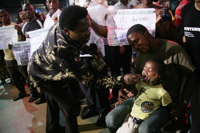 TB Joshua sprays Anointing Water on Joshua during The SCOAN healing service